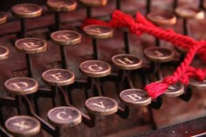 close up vintage typewriter keys with red cord